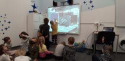 Dzieci siedzą na dywanie. Jedno z nich wykonuje zadanie na tablicy interaktywnej
