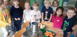 Dzieci na około stolika, pozują do zdjęcia z sokowirówką, na której przed chwilą wykonały sok