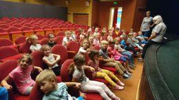 dzieci siedzą na sali, na widowni Teatru Arlekin