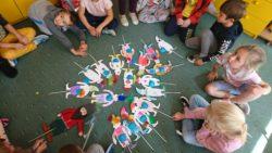 Dzieci siedzą wkole na dywanie. Na środku leżą wykonane przez nie pacynki skrzatów
