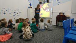Dzieci siedzą na dywanie. Oglądają prezentację do nauki języka angielskiego