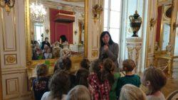 Dzieci w sali Pałacu pod Blachą stoja na przeciwko wielkiego złotego lustra. Na przeciwko nich pani przewodnik