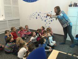Lektorka angielskiego tłumaczy coś siedzącym na przeciwko niej dzieciom