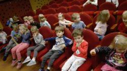 Dzieci siedzą na widowni, na fotelach w Teatrze Arlekin