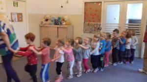 Dzieci prowadzone przez panią nauczycielkę poruszają się w pociągu po sali