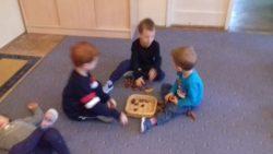 Dzieci liczące i układające kasztany na dywanie