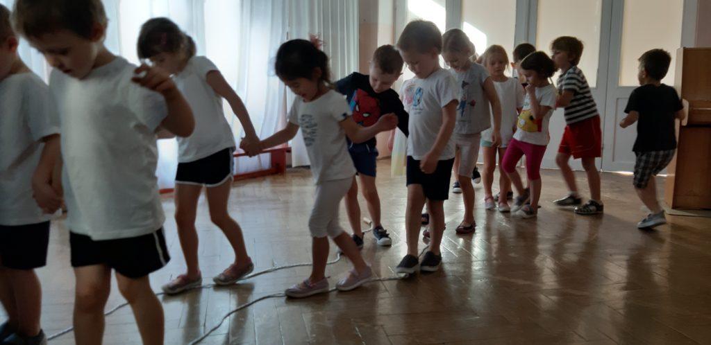 Dzieci w strojach gimnastycznych idą noga za nogą po skakance