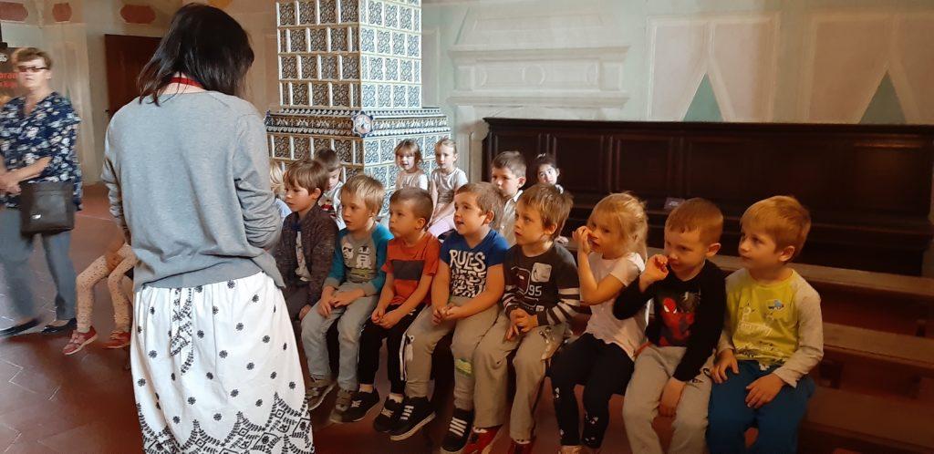 Dzieci siedzą na ławkach w zamku słuchając pani przewodnik