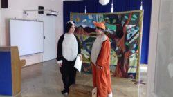 Dwóch aktorów przebranych za lisa i borsuka stoi na tle dekoracji lasu