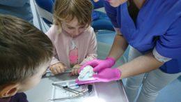Dziewczynka pochyla się nad odciskiem zębów. Obok stoi pani dentyska