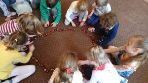 dzieci układają kasztany w koło na dywanie