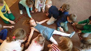 dzieci układają kasztany na około leżącej dziewczynki