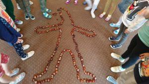 sylweta człowieka ułożona przez dzieci na dywanie z kasztanów