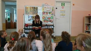 dzieci słuchają mamy czytającej książeczkę