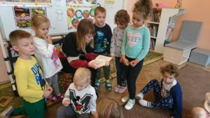 Dzieci stoją na około Mamy Maritki, która czyta im książeczkę