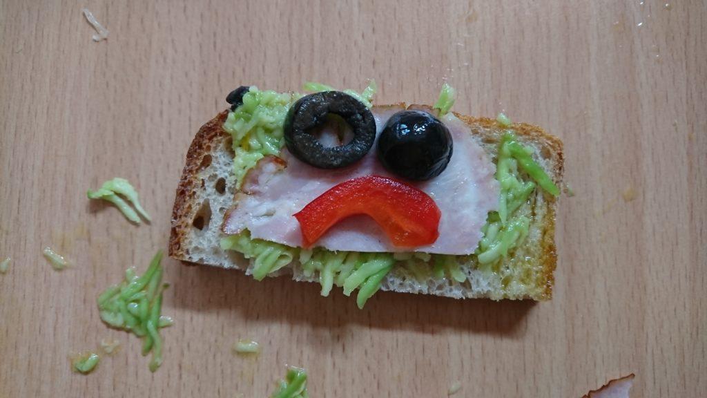 Zdjęcie kanapki z szynką, sałatą, oliwkami i papryką. Warzywa są ułożone w buzię