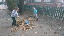 dzieci grabiące liście w ogrodzie