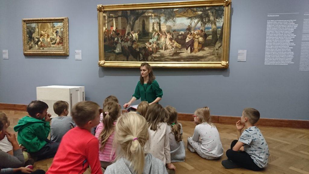 Dzieci siedzą na podłodze w Muzeum. W tle widać obrazy.