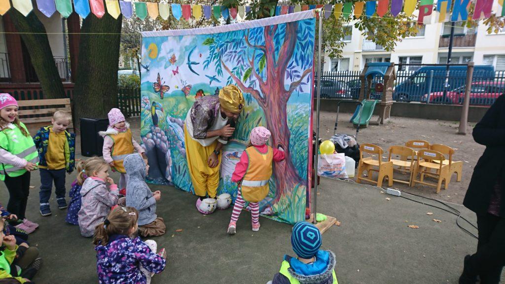 Dzieci w ogrodzie przedszkolnym, stoją przed dekoracją lasu. Aktor mówi coś do jednego z nich. Jest przebrany za Alladyna
