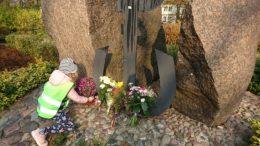 Dziewczynka składa kwiaty pod pomnikiem Polski Walczącej