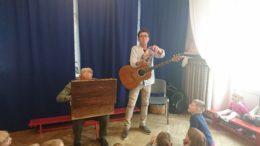 PRzed dziećmi stoi Gucio z przewieszoną przez ramie gitarą. Obok siedzi Duduś i szuka czegoś w starym kufrze