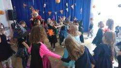 Dzieci w trojach halloweenowych tańczą w sali rytmicznej na tle halloweenowych dekoracji