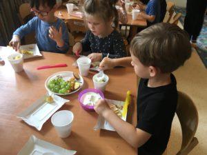 Dzieci siedzą przy stolikach, wykonują własnego pomysłu jogurty. Przed nimi leżą winogrona, serki i jabłka