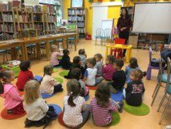 Dzieci siedzą na podłodze na kolorowych dywanikach. Przed nimi stoi pani bibliotekarka na tle książek