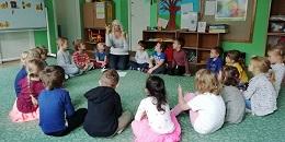 Dzieci siedzą w kole na dywanie. Słuchają nauczycielki