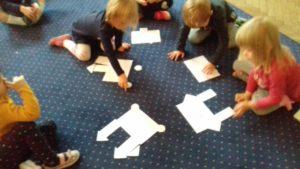 Dzieci układają na dywanie zamki z figur geometrycznych