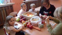 Dzieci siedzą przy stoliku, na którym leżą owoce i warzywa. Obserwują jak panie obierają owoce na sok