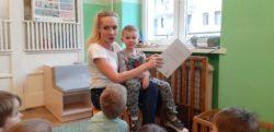 Leon siedzi Mamie na kolanach, która czyta dzieciom ksiązeczkę