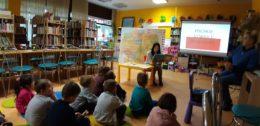 Dzieci siedzą na kolorowych dywanikach patrząc się na obraz wyświetlany z projektora. Obraz przedstawia flagę Polski. Przed dziećmi siedzi również pani bibliotekarka czytając książkę