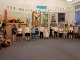 Dzieci ubrane na galowo stoją w szeregu na tle napisu: pasowanie na przedszkolaka