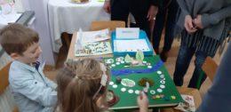 Dzieci grają w grę planszową wykonaną przez siebie