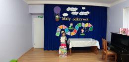 Dziecko pozujące do zdjęcia na tale dekoracji konkursu Mały odkrywca