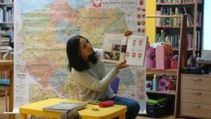 Pani bibliotekarka siedzi na tle mapy Polski prezentując dzieciom książeczkę o godle Polski