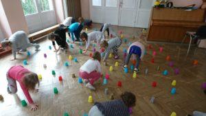 dzieci czworakują pomiędzy rozłożonymi kubeczkami na sali
