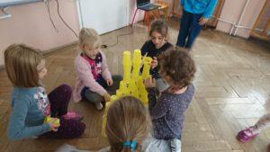grupa dzieci buduje zamek z kubeczków