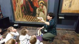 Dzieci siedzą na podłodze w sali Muzeum Warszawy. Pani przewodnik pokazuje im narzędzia malarskie. W tle widać obraz