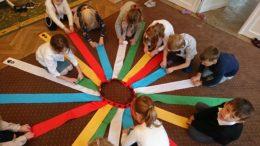 dzieci bawią się i zwijają kolorowe szarfy