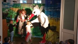 Na scenie na tle dekoracji lasu stoi para aktorów przebranych za bociana i wieśniaczkę. Rozmawiają z dziećmi zaproszonymi na scenę