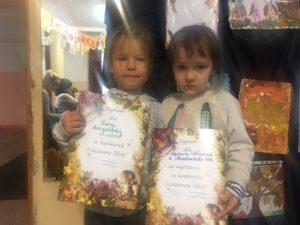 Dwie dziewczynki stoją na tle prac konkursowych i prezentują swoje dyplomy