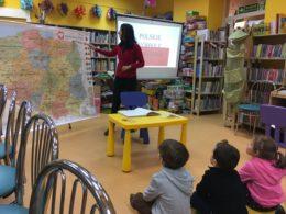 Dzieci siedzą na podłodze. Pani bibliotekarka wskazuje coś na mapie, która jest rozłożona przed nimi. W tle jest włączony projektor wyświetlający flagę Polski