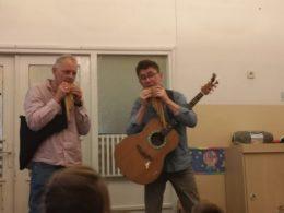 Przed dziećmi stoi Gucio i Duduś, którzy grają na fletni andyjskiej. Gucio ma przewieszoną przez ramię gitarę