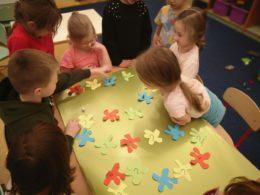 dzieci grające w wykonaną przez siebie grę planszową