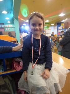 uśmiechnięta dziewczynka z medalem na szyi