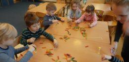 Dzieci siedzą przy złączonych stołach, na których jest rozsypany makaron