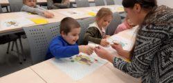 Pani prowadząca spotkanie pomaga dwojgu dzieci siedzącym przy stoliku wykonać doświadczenie fizyczne