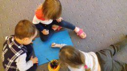 dzieci rysujące na kartkach pastelami